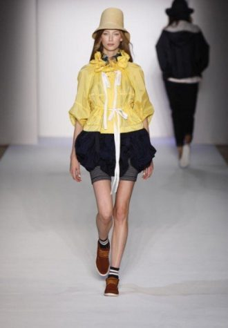 dámský béžový klobouk, žlutá pršiplášť a tmavě modrá sukně s legíny Karen Walker