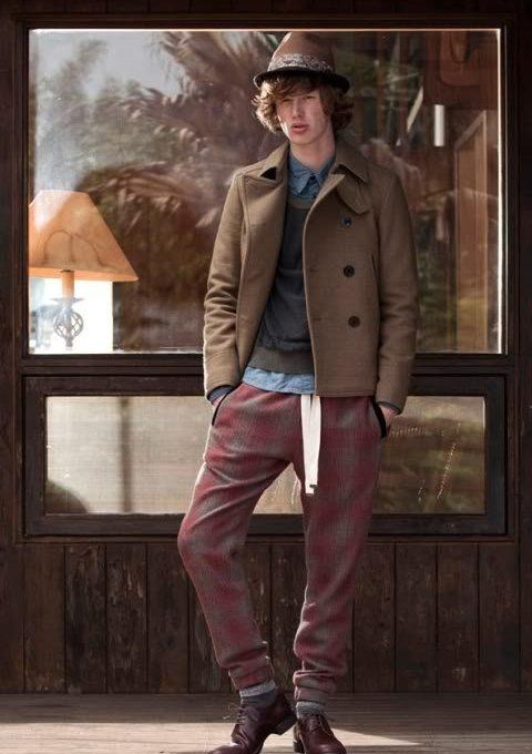 pánský hnědý klobouk, hnědý kabát, šedý svetr a kostkované kalhoty FACTOTUM