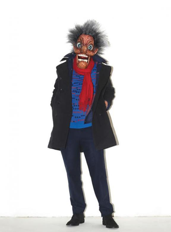 Šílený správce zkouší omládnou v trenčkotu, modrém svetru a výrazné šále.