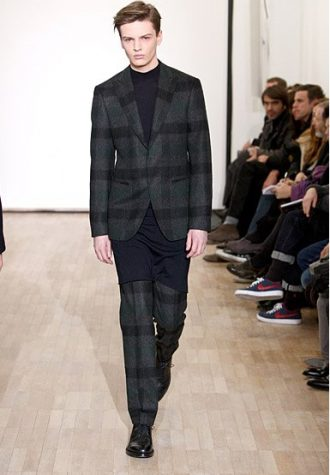 pánský kostkovaný oblek a černý prodloužený svetr Raf Simons