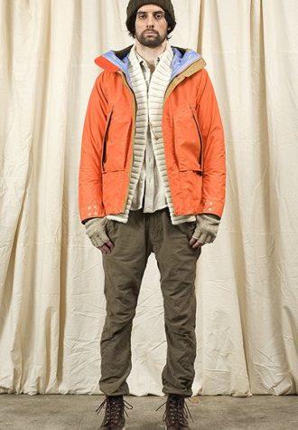 pánská hnědá čepice, oranžová bunda, bílý svetr a hnědé kalhoty Nonnative
