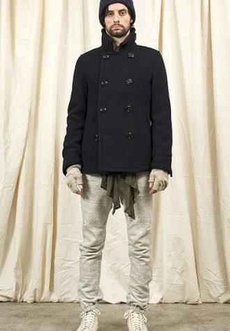 pánská modrá čepice, kabát a světle béžové kalhoty Nonnative